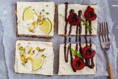Ακατέργαστα cheesecakes φυστικιών, καρύδων, ασβέστη και σοκολάτα-κερασιών Στοκ Εικόνα