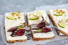 Ακατέργαστα cheesecakes φυστικιών, καρύδων, ασβέστη και σοκολάτα-κερασιών Στοκ Φωτογραφία