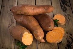 Ακατέργαστες γλυκές πατάτες στο αγροτικό ξύλινο υπόβαθρο στοκ εικόνες