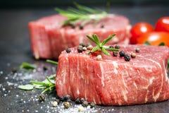 Ακατέργαστες μπριζόλες βόειου κρέατος με τα καρυκεύματα και Rosemary πέρα από την πλάκα Στοκ φωτογραφία με δικαίωμα ελεύθερης χρήσης
