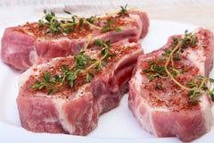 Ακατέργαστες μπριζόλες, καρυκεύματα και δεντρολίβανο χοιρινού κρέατος στον τέμνοντα πίνακα Έτοιμος για το μαγείρεμα Στοκ φωτογραφία με δικαίωμα ελεύθερης χρήσης