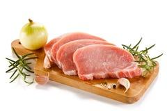 Ακατέργαστες μπριζόλες χοιρινού κρέατος στον τέμνοντες πίνακα και τα λαχανικά Στοκ Εικόνες