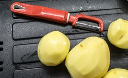 Ακατέργαστες πατάτες και ένα μαχαίρι Στοκ Εικόνες