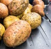 Ακατέργαστες πατάτες στον πίνακα Στοκ Εικόνες