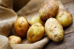 Ακατέργαστες πατάτες burlap στο υπόβαθρο Στοκ Φωτογραφίες