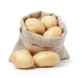 Ακατέργαστες φρέσκες πατάτες burlap στην τσάντα που απομονώνεται στο λευκό Στοκ Φωτογραφία