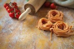 Ακατέργαστες φωλιές tagliatelle άψητες στον ξύλινο πίνακα με το αλεύρι και τις ντομάτες στοκ φωτογραφία