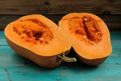 Ακατέργαστη γλυκιά κολοκύθα που κόβεται στα μισά στον εκλεκτής ποιότητας ξύλινο πίνακα Στοκ Φωτογραφία