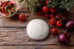Ακατέργαστη ζύμη για την πίτσα με το ξύλινο υπόβαθρο συστατικών Στοκ εικόνες με δικαίωμα ελεύθερης χρήσης