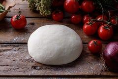 Ακατέργαστη ζύμη για την πίτσα με το ξύλινο υπόβαθρο συστατικών Στοκ εικόνα με δικαίωμα ελεύθερης χρήσης