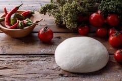 Ακατέργαστη ζύμη για την πίτσα με το ξύλινο υπόβαθρο συστατικών Στοκ Εικόνες