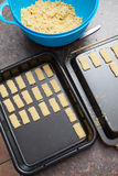 Ακατέργαστη ζύμη μπισκότων που κόβεται και που συσκευάζεται επάνω στο δίσκο ψησίματος Στοκ Εικόνες