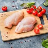 Ακατέργαστη λωρίδα στηθών κοτόπουλου με τα πράσινα, τις ντομάτες και τα καρυκεύματα σε ένα σκοτεινό υπόβαθρο στοκ φωτογραφία με δικαίωμα ελεύθερης χρήσης
