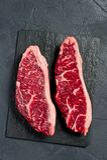 Ακατέργαστη μπριζόλα κεκλιμένων ραμπών βόειου κρέατος Μαύρο υπόβαθρο, τοπ άποψη στοκ εικόνες με δικαίωμα ελεύθερης χρήσης