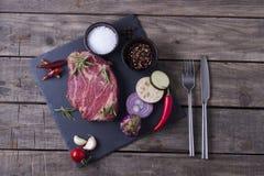 Ακατέργαστη μπριζόλα κρέατος από το μαρμάρινο βόειο κρέας με τα λαχανικά και τα καρυκεύματα στο πιάτο πετρών Τοπ όψη Στοκ φωτογραφία με δικαίωμα ελεύθερης χρήσης