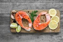Ακατέργαστη μπριζόλα σολομών με το χορτάρι, το λεμόνι και peppercorns στον ξύλινο τέμνοντα πίνακα Υγιή και τρόφιμα διατροφής Στοκ φωτογραφία με δικαίωμα ελεύθερης χρήσης