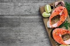 Ακατέργαστη μπριζόλα σολομών με το χορτάρι, το λεμόνι και peppercorns στον ξύλινο τέμνοντα πίνακα Υγιή και τρόφιμα διατροφής Τοπ  Στοκ φωτογραφίες με δικαίωμα ελεύθερης χρήσης