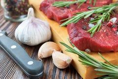 Ακατέργαστη μπριζόλα βόειου κρέατος με τα λαχανικά και τα καρυκεύματα Στοκ Εικόνες