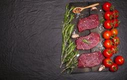 Ακατέργαστη μπριζόλα βόειου κρέατος σε έναν πίνακα κοπής με τα λαχανικά και τα καρυκεύματα Στοκ φωτογραφίες με δικαίωμα ελεύθερης χρήσης