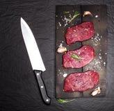 Ακατέργαστη μπριζόλα βόειου κρέατος σε έναν πίνακα κοπής με τις ντομάτες δεντρολιβάνου και κερασιών Στοκ Εικόνες