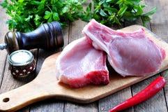 Ακατέργαστη μπριζόλα χοιρινού κρέατος στο κόκκαλο με το άλας μαϊντανού, μεντών, πιπεριών και θάλασσας στοκ εικόνα