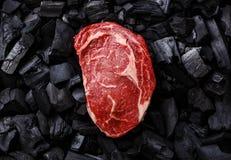 Ακατέργαστη μπριζόλα Ribeye κρέατος στον ξυλάνθρακα Στοκ εικόνες με δικαίωμα ελεύθερης χρήσης