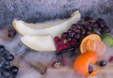 Ακατέργαστη οργανική πιατέλα φρούτων με τα πεπόνια και τα σταφύλια μούρων Στοκ Εικόνες