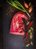 Ακατέργαστη λωρίδα βόειου κρέατος στο σκοτεινό υπόβαθρο με τα καρυκεύματα Στοκ Εικόνες