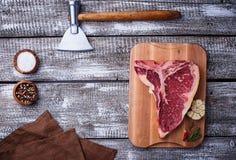 Ακατέργαστη T-bone μπριζόλα με το τσεκούρι Στοκ εικόνα με δικαίωμα ελεύθερης χρήσης