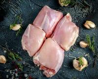 Ακατέργαστοι ελεύθεροι μηροί κοτόπουλου σειράς ανόστεοι skinless με το thime, το σκόρδο, τα δημητριακά κόκκινων πιπεριών και τις  Στοκ Εικόνες