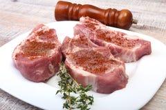 Ακατέργαστοι μπριζόλες χοιρινού κρέατος και μύλος καρυκευμάτων στον τέμνοντα πίνακα Έτοιμος για το μαγείρεμα Στοκ Φωτογραφία