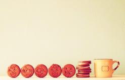 Ακατέργαστος των μπισκότων με το πρόσωπο smiley πέρα από τον ξύλινο πίνακα δίπλα στο φλιτζάνι του καφέ η εικόνα είναι αναδρομικό  Στοκ εικόνα με δικαίωμα ελεύθερης χρήσης