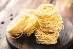 Ακατέργαστος όλα τα ζυμαρικά uovo `, νουντλς αυγών στο σκοτεινό ξύλινο αγροτικό υπόβαθρο Στοκ Φωτογραφίες