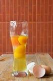 Ακατέργαστο αυγό με τον κίτρινο λέκιθο σε ένα γυαλί και σπασμένα μισά της Shell Στοκ εικόνα με δικαίωμα ελεύθερης χρήσης
