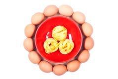 Ακατέργαστο αυγό τρία ζυμαρικών κύκλοι στο κόκκινο πιάτο σε έναν στρογγυλό τέμνοντα κάπρο Στοκ Εικόνες