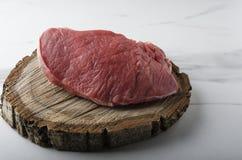 Ακατέργαστο κομμάτι του βόειου κρέατος στην κοπή του ξύλινου πίνακα στοκ φωτογραφία με δικαίωμα ελεύθερης χρήσης