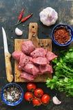 Ακατέργαστο κρέας βόειου κρέατος που κόβεται στα κομμάτια, τα καρυκεύματα, τις ντομάτες κερασιών, το σκόρδο και το μαϊντανό Η άπο στοκ εικόνες με δικαίωμα ελεύθερης χρήσης