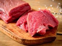 Ακατέργαστο κρέας βόειου κρέατος στον αγροτικό ξύλινο τέμνοντα πίνακα Στοκ φωτογραφία με δικαίωμα ελεύθερης χρήσης