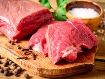 Ακατέργαστο κρέας βόειου κρέατος στον αγροτικό ξύλινο τέμνοντα πίνακα Στοκ Εικόνα