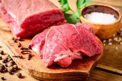 Ακατέργαστο κρέας βόειου κρέατος στον αγροτικό ξύλινο τέμνοντα πίνακα Στοκ Φωτογραφία