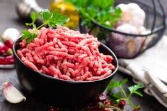 Ακατέργαστο κρέας επίγειου βόειου κρέατος με τα συστατικά για το μαγείρεμα κρέας που κομματιάζεται & στοκ φωτογραφίες