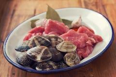 Ακατέργαστο κρέας με το σκόρδο και μαλάκια στο πιάτο Στοκ εικόνα με δικαίωμα ελεύθερης χρήσης