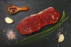 Ακατέργαστο κρέας μπριζόλας βόειου κρέατος που κόβονται και καρυκεύματα στο μαύρο πίνακα Στοκ Εικόνες