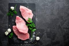 Ακατέργαστο κρέας, μπριζόλες της Τουρκίας στο μαύρο υπόβαθρο, τοπ άποψη στοκ φωτογραφία με δικαίωμα ελεύθερης χρήσης