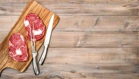 Ακατέργαστο κρέατος πλευρών ματιών υπόβαθρο επιτραπέζιων τροφίμων κουζινών μπριζόλας ξύλινο Στοκ Φωτογραφίες