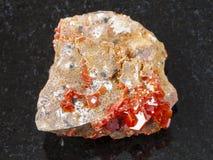 ακατέργαστο κρύσταλλο του πολύτιμου λίθου Vanadinite στο σκοτάδι Στοκ Φωτογραφία