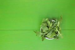 Ακατέργαστο μαρούλι arugula σε ένα άσπρο πιάτο σε έναν ξύλινο πίνακα Στοκ Εικόνες