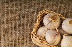 Ακατέργαστο μικρό σκόρδο στο καλάθι στο burlap υπόβαθρο στοκ εικόνες με δικαίωμα ελεύθερης χρήσης