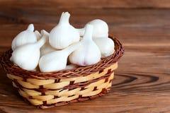 Ακατέργαστο ολόκληρο σκόρδο σε ένα καλάθι σε ένα ξύλινο υπόβαθρο Flavorful προϊόν, θεραπευτικά τρόφιμα closeup Στοκ εικόνα με δικαίωμα ελεύθερης χρήσης