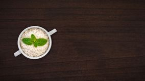 Ακατέργαστο ρύζι στο κύπελλο σούπας στην ξύλινη επιτραπέζια κορυφή με το φύλλο μεντών Στοκ φωτογραφία με δικαίωμα ελεύθερης χρήσης